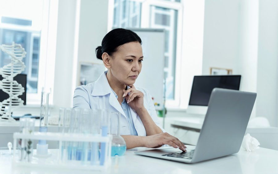 Researcher in lab sourcing samples using laptop